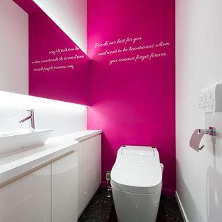 Идея дизайна: туалет среднего размера в современном стиле с фасадами островного типа, белыми фасадами, унитазом-моноблоком, розовыми стенами, полом из керамогранита, настольной раковиной, столешницей из ламината, черным полом и белой столешницей
