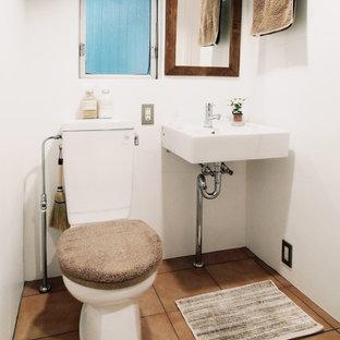 Ispirazione per un piccolo bagno di servizio minimalista con nessun'anta, WC a due pezzi, piastrelle bianche, pareti bianche, pavimento in terracotta e lavabo sospeso