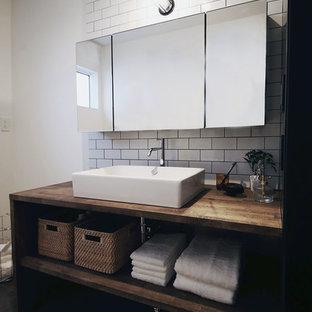 Imagen de aseo urbano con armarios abiertos, puertas de armario de madera en tonos medios, baldosas y/o azulejos blancos, paredes blancas, lavabo sobreencimera, encimera de madera, suelo negro y encimeras marrones