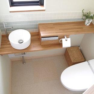 Свежая идея для дизайна: маленький туалет в скандинавском стиле с унитазом-моноблоком, белой плиткой, удлиненной плиткой, белыми стенами, врезной раковиной, бежевым полом, коричневой столешницей и полом из винила - отличное фото интерьера
