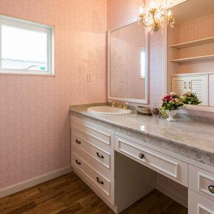 Свежая идея для дизайна: большой туалет в скандинавском стиле с фасадами островного типа, коричневыми фасадами, унитазом-моноблоком, розовой плиткой, керамической плиткой, розовыми стенами, паркетным полом среднего тона, монолитной раковиной, мраморной столешницей, коричневым полом, белой столешницей, напольной тумбой, потолком с обоями и обоями на стенах - отличное фото интерьера