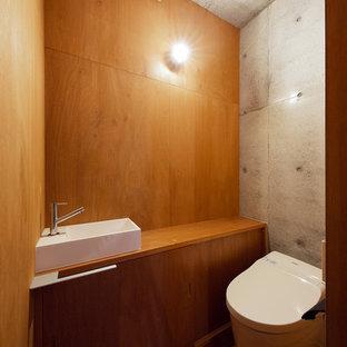 他の地域のインダストリアルスタイルのおしゃれなトイレ・洗面所 (フラットパネル扉のキャビネット、中間色木目調キャビネット、マルチカラーの壁、無垢フローリング、ベッセル式洗面器、木製洗面台、茶色い床、ブラウンの洗面カウンター) の写真