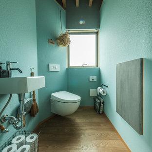 他の地域のアジアンスタイルのおしゃれなトイレ・洗面所 (青い壁、無垢フローリング、壁付け型シンク、茶色い床) の写真