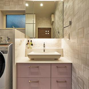 Modelo de aseo minimalista, pequeño, con armarios con paneles lisos, puertas de armario violetas, paredes grises, lavabo sobreencimera y suelo beige