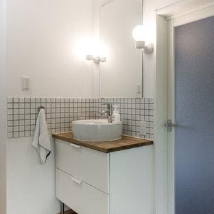 Пример оригинального дизайна: туалет среднего размера в скандинавском стиле с плоскими фасадами, белыми фасадами, белыми стенами, деревянным полом, настольной раковиной и коричневым полом