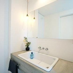 他の地域のコンテンポラリースタイルのおしゃれなトイレ・洗面所 (白い壁、オーバーカウンターシンク、コンクリートの洗面台、グレーの床、グレーの洗面カウンター) の写真