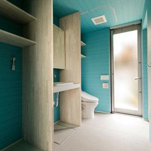Свежая идея для дизайна: маленький туалет в стиле модернизм с открытыми фасадами, раздельным унитазом, синими стенами, бетонным полом, монолитной раковиной, серым полом, белой столешницей, потолком с обоями и обоями на стенах - отличное фото интерьера