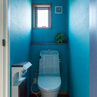 他の地域のコンテンポラリースタイルのおしゃれなトイレ・洗面所 (青い壁、無垢フローリング、茶色い床) の写真