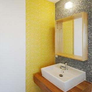 Пример оригинального дизайна: маленький туалет в стиле модернизм с открытыми фасадами, темными деревянными фасадами, синей плиткой, плиткой мозаикой, желтыми стенами, полом из линолеума, подвесной раковиной и столешницей из дерева