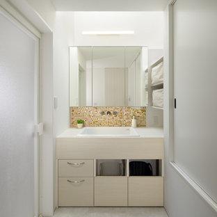 他の地域のモダンスタイルのおしゃれなトイレ・洗面所 (フラットパネル扉のキャビネット、ベージュのキャビネット、白い壁、オーバーカウンターシンク、グレーの床) の写真