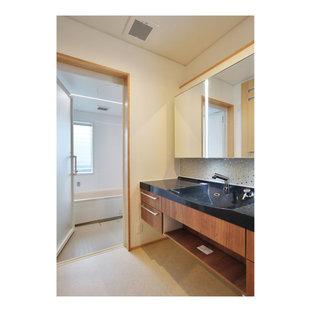 Immagine di un bagno di servizio minimalista con ante di vetro, ante grigie, mobile bagno incassato, piastrelle verdi, piastrelle a mosaico, top grigio, pareti beige, lavabo integrato e top in superficie solida