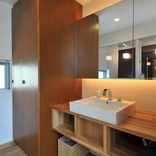 東京23区の小さいコンテンポラリースタイルのおしゃれなトイレ・洗面所 (フラットパネル扉のキャビネット、茶色いキャビネット、白い壁、無垢フローリング、ベッセル式洗面器、木製洗面台、茶色い床、ブラウンの洗面カウンター) の写真