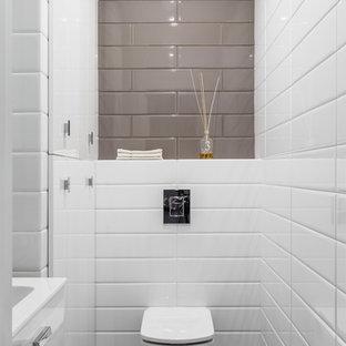 京都のコンテンポラリースタイルのおしゃれなトイレ・洗面所 (フラットパネル扉のキャビネット、白いキャビネット、壁掛け式トイレ、グレーのタイル、白いタイル、サブウェイタイル、マルチカラーの壁、グレーの床) の写真