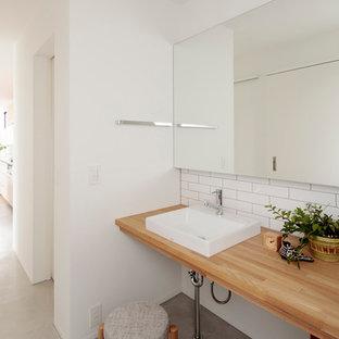他の地域の北欧スタイルのおしゃれなトイレ・洗面所 (白い壁、コンクリートの床、ベッセル式洗面器、木製洗面台、グレーの床、ブラウンの洗面カウンター) の写真