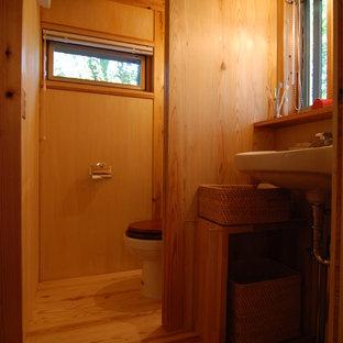 他の地域の小さいラスティックスタイルのおしゃれなトイレ・洗面所 (一体型トイレ、合板フローリング、壁付け型シンク、オープンシェルフ、ガラスタイル) の写真