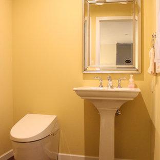 他の地域のトラディショナルスタイルのおしゃれなトイレ・洗面所 (黄色い壁、濃色無垢フローリング、コンソール型シンク、茶色い床) の写真