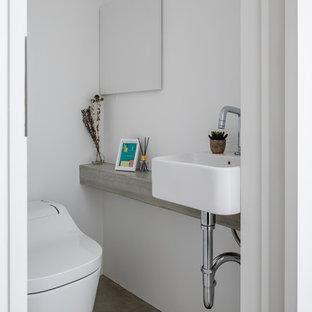 他の地域のコンテンポラリースタイルのおしゃれなトイレ・洗面所 (一体型トイレ、白い壁、コンクリートの床、ベッセル式洗面器、コンクリートの洗面台、グレーの床、グレーの洗面カウンター) の写真