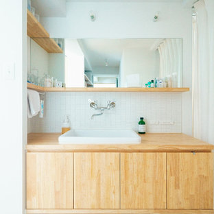 Foto de aseo de estilo zen con armarios con paneles lisos, puertas de armario de madera oscura, baldosas y/o azulejos blancos, paredes blancas, lavabo encastrado y suelo blanco