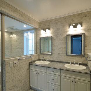 東京23区のヴィクトリアン調のおしゃれなトイレ・洗面所 (レイズドパネル扉のキャビネット、白いキャビネット、グレーの壁、御影石の洗面台、グレーの床) の写真