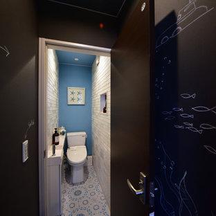 他の地域の小さいビーチスタイルのおしゃれなトイレ・洗面所 (フラットパネル扉のキャビネット、白いキャビネット、マルチカラーの床、一体型トイレ、白いタイル、セラミックタイル、青い壁、クッションフロア、一体型シンク、人工大理石カウンター、白い洗面カウンター) の写真