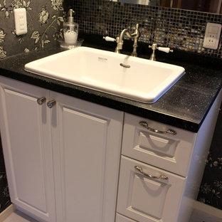 名古屋の小さいトラディショナルスタイルのおしゃれなトイレ・洗面所 (レイズドパネル扉のキャビネット、白いキャビネット、黒いタイル、白いタイル、モザイクタイル、グレーの壁、大理石の床、オーバーカウンターシンク、テラゾーの洗面台) の写真