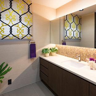 他の地域のコンテンポラリースタイルのおしゃれなトイレ・洗面所 (フラットパネル扉のキャビネット、グレーの壁、グレーの床、茶色いキャビネット、マルチカラーのタイル、モザイクタイル、アンダーカウンター洗面器、白い洗面カウンター) の写真