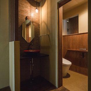 Diseño de aseo asiático con paredes marrones, suelo de madera oscura, lavabo tipo consola y suelo marrón