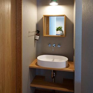 他の地域のコンテンポラリースタイルのおしゃれなトイレ・洗面所 (オープンシェルフ、グレーの壁、無垢フローリング、ベッセル式洗面器、木製洗面台、茶色い床、ブラウンの洗面カウンター) の写真