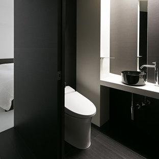 Пример оригинального дизайна: туалет в стиле модернизм с белыми стенами, темным паркетным полом и настольной раковиной