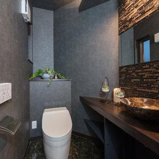 На фото: туалеты среднего размера в стиле модернизм с открытыми фасадами, унитазом-моноблоком, коричневой плиткой, плиткой мозаикой, серыми стенами, полом из линолеума, накладной раковиной, столешницей из дерева, коричневым полом и коричневой столешницей