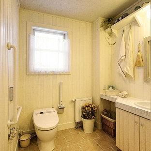 Idee per un bagno di servizio country con ante in stile shaker, ante con finitura invecchiata, WC sospeso, piastrelle bianche, pareti bianche, pavimento in terracotta, top piastrellato e pavimento beige
