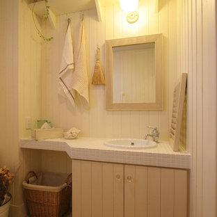 Foto di un bagno di servizio country con ante in stile shaker, ante con finitura invecchiata, WC sospeso, piastrelle bianche, pareti bianche, pavimento in terracotta, top piastrellato e pavimento beige