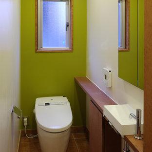 Idee per un bagno di servizio moderno con WC monopezzo, pareti verdi, pavimento in terracotta, lavabo a bacinella, top in legno e ante in legno scuro