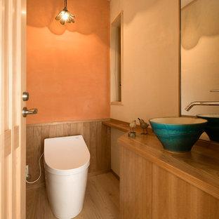 Удачное сочетание для дизайна помещения: туалет в классическом стиле с плоскими фасадами, фасадами цвета дерева среднего тона, оранжевыми стенами, деревянным полом, настольной раковиной и коричневым полом - самое интересное для вас