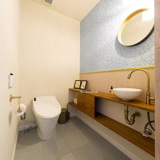 他の地域のコンテンポラリースタイルのおしゃれなトイレ・洗面所 (オープンシェルフ、ピンクのタイル、モザイクタイル、白い壁、セラミックタイルの床、オーバーカウンターシンク、木製洗面台、ブラウンの洗面カウンター) の写真