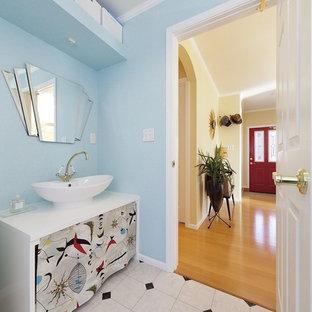 東京23区のビーチスタイルのおしゃれなトイレ・洗面所 (オープンシェルフ、白いキャビネット、青い壁、ベッセル式洗面器、マルチカラーの床) の写真