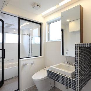 東京23区のコンテンポラリースタイルのおしゃれなトイレ・洗面所 (白い壁、ベッセル式洗面器、グレーの床、青い洗面カウンター) の写真