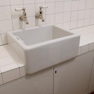 Immagine di un bagno di servizio minimalista con ante lisce, ante beige, piastrelle bianche, piastrelle in ceramica, pareti bianche, pavimento in terracotta, lavabo a bacinella, top piastrellato, pavimento marrone e top bianco