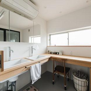 Cette image montre un très grand WC et toilettes asiatique avec un mur blanc, un lavabo posé, un plan de toilette en bois, un sol gris, un plan de toilette marron, un placard sans porte, des portes de placard beiges et béton au sol.