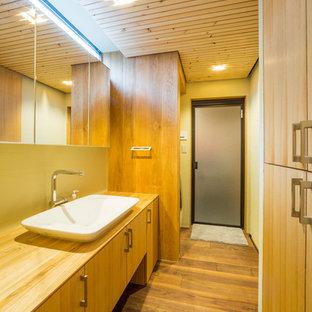 Idées déco pour un WC et toilettes moderne avec un placard à porte plane, des portes de placard en bois brun, un mur jaune, un sol en bois foncé, une vasque, un plan de toilette en bois, un sol marron et un plan de toilette marron.