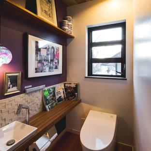 Новый формат декора квартиры: туалет в скандинавском стиле с унитазом-моноблоком, фиолетовыми стенами, темным паркетным полом, коричневым полом, настольной раковиной, столешницей из дерева и коричневой столешницей