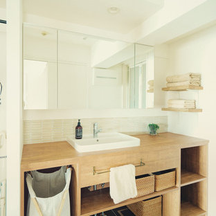 名古屋の北欧スタイルのおしゃれなトイレ・洗面所 (オープンシェルフ、中間色木目調キャビネット、白い壁、ベッセル式洗面器、木製洗面台、黒い床) の写真