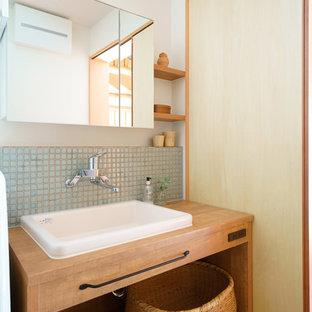 Ejemplo de aseo de estilo zen con armarios abiertos, puertas de armario de madera oscura, paredes blancas, lavabo sobreencimera y encimera de madera