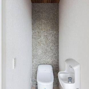 Ejemplo de aseo moderno, pequeño, con bidé, paredes grises, suelo de contrachapado, lavabo tipo consola y suelo beige