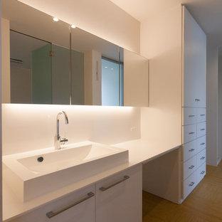 Idee per un bagno di servizio moderno con ante a filo, ante bianche, piastrelle bianche, pavimento in linoleum, lavabo a consolle, top in superficie solida e pavimento beige