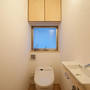 他の地域の小さいモダンスタイルのおしゃれなトイレ・洗面所 (フラットパネル扉のキャビネット、淡色木目調キャビネット、白い壁、無垢フローリング、コンソール型シンク、茶色い床) の写真