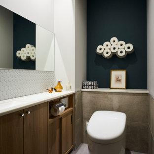 他の地域の中くらいのコンテンポラリースタイルのおしゃれなトイレ・洗面所 (フラットパネル扉のキャビネット、中間色木目調キャビネット、壁掛け式トイレ、白いタイル、緑の壁、磁器タイルの床、アンダーカウンター洗面器、グレーの床、白い洗面カウンター、造り付け洗面台) の写真