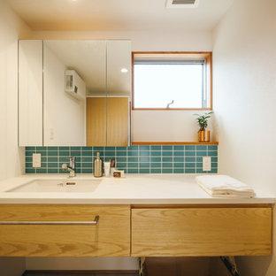 Mid-Century Gästetoilette mit flächenbündigen Schrankfronten, weißen Schränken, grünen Fliesen, Metrofliesen, weißer Wandfarbe, braunem Holzboden, Mineralwerkstoff-Waschtisch, weißer Waschtischplatte, eingebautem Waschtisch, Tapetendecke und Tapetenwänden in Sonstige
