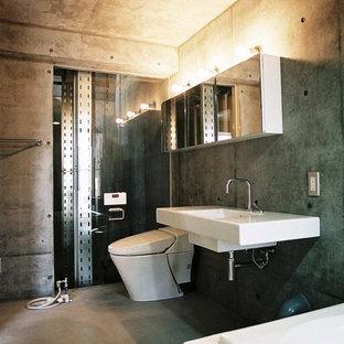 東京都下のコンテンポラリースタイルのおしゃれなトイレ・洗面所 (グレーの壁、壁付け型シンク、グレーの床) の写真