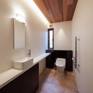 Свежая идея для дизайна: туалет в стиле модернизм с плоскими фасадами, темными деревянными фасадами, белыми стенами, полом из терракотовой плитки, настольной раковиной и коричневым полом - отличное фото интерьера